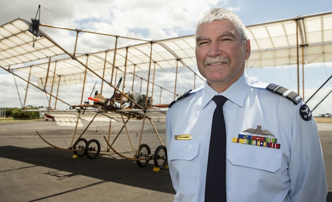 Air Vice-Marshal Mark Skidmore stands in front of a replica Bristol Boxkite that he piloted on its maiden flight at RAAF Base Williams, Point Cook.